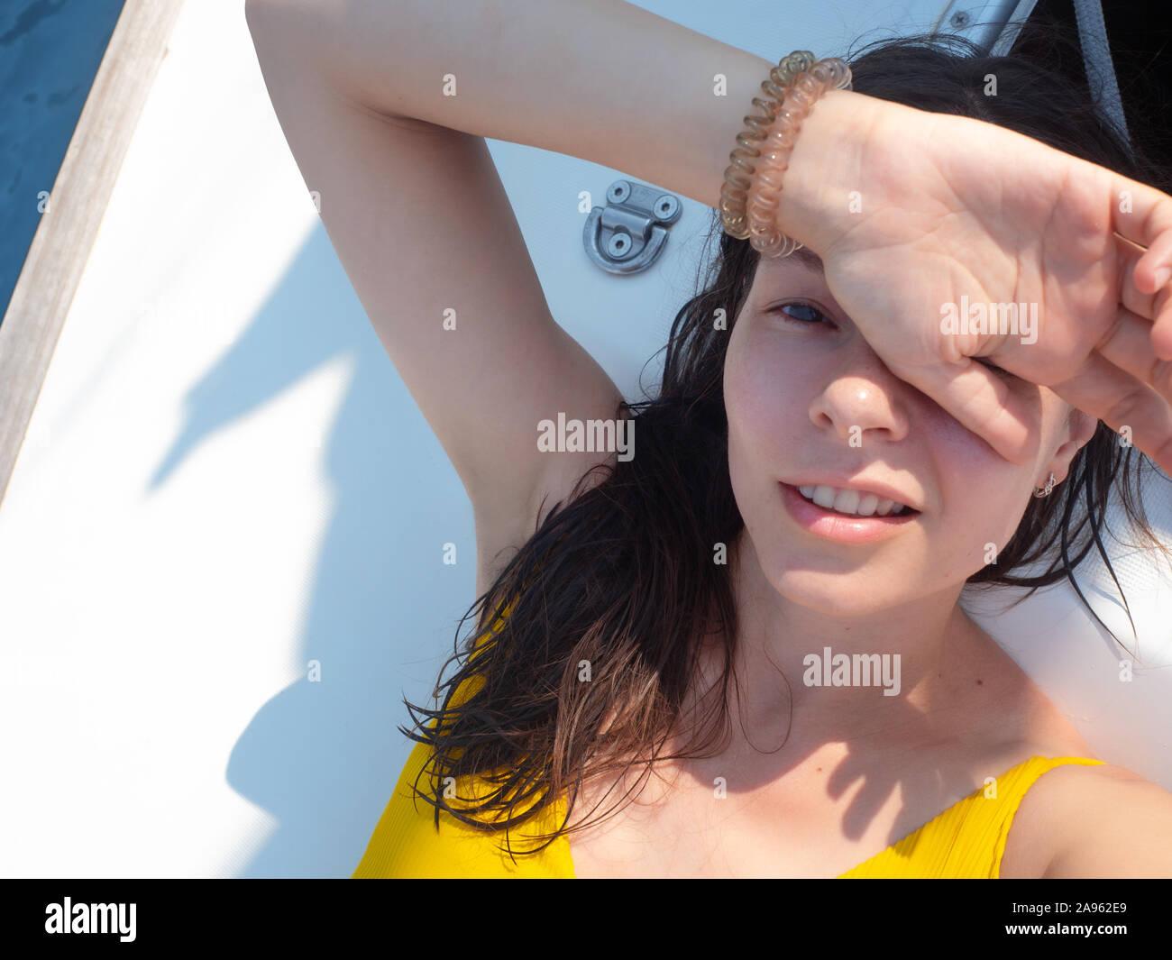 Giovane donna in un giallo brillante in pezzo unico costume da bagno a prendere il sole sul ponte di una barca a vela. Vacanze al mare, scottature e protezione solare. Foto Stock