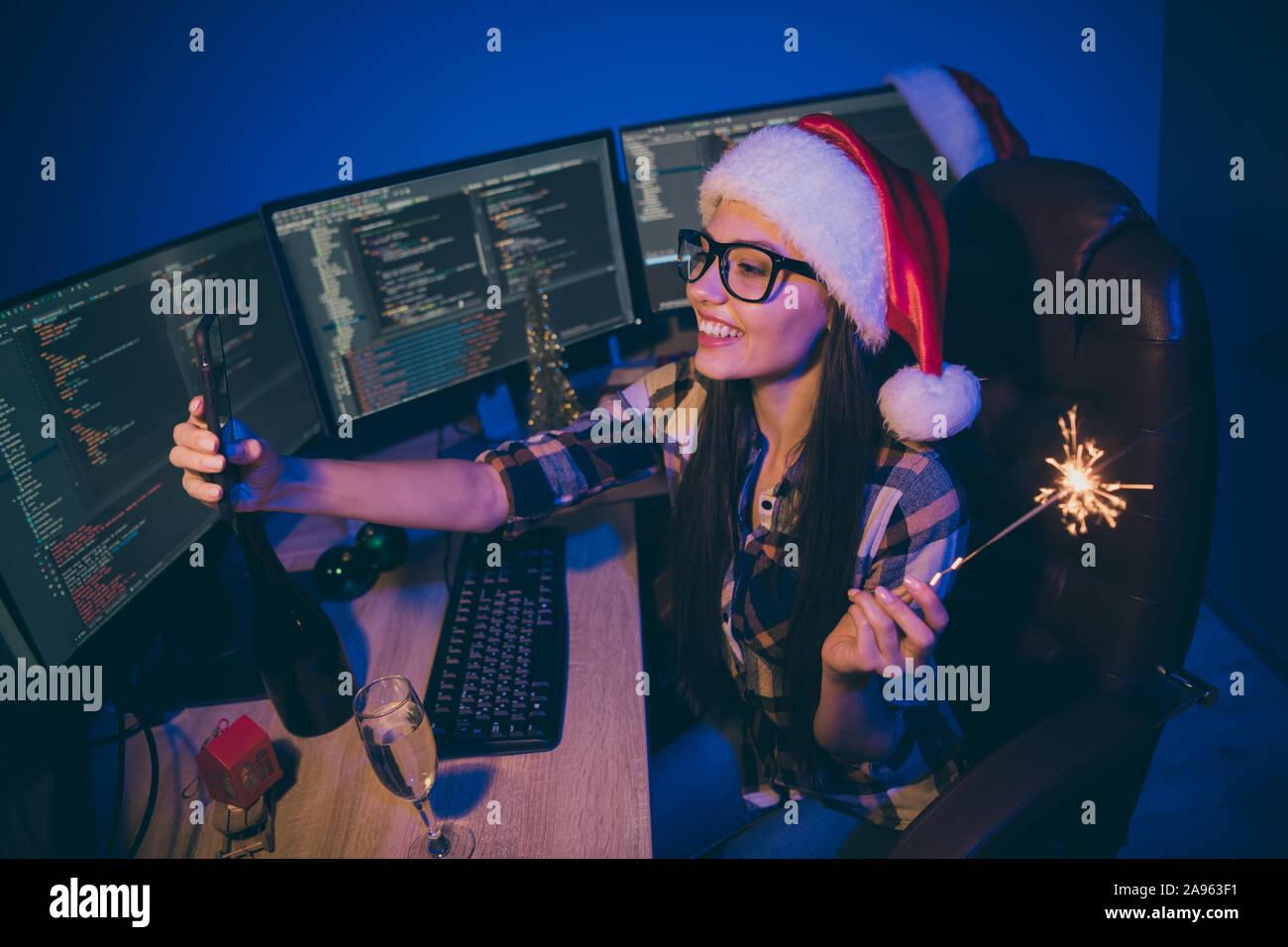 Foto di lavoro coder lady notte di lavoro soddisfare newyear office tenere premuto Telefono sparkler tenendo selfies bere il vino parla di skype usura parenti babbo natale Foto Stock