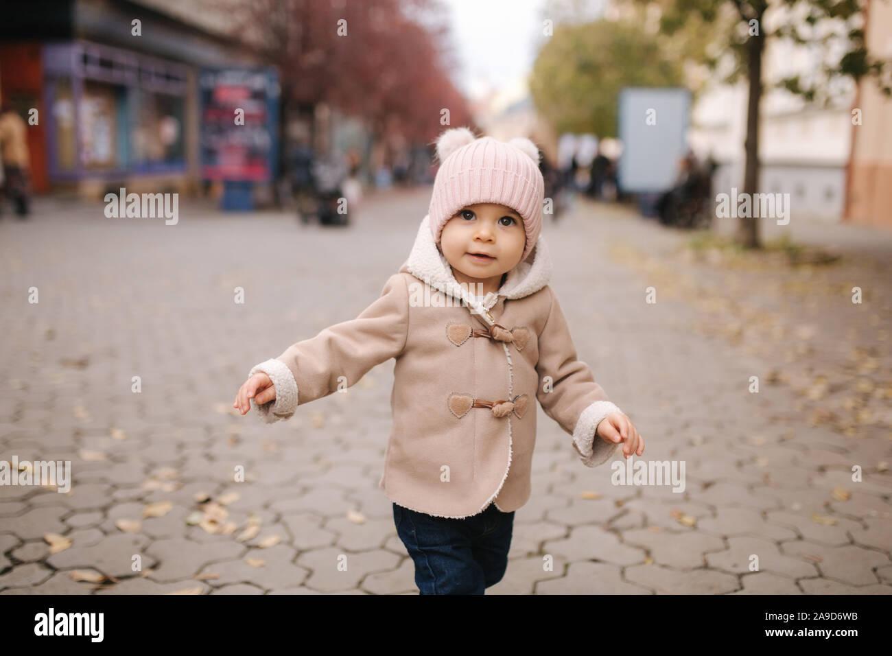 Adorabili poco Baby girl nel bellissimo cappotto marrone a piedi nella città. Carino undici mese baby sorriso ed eseguire Foto Stock
