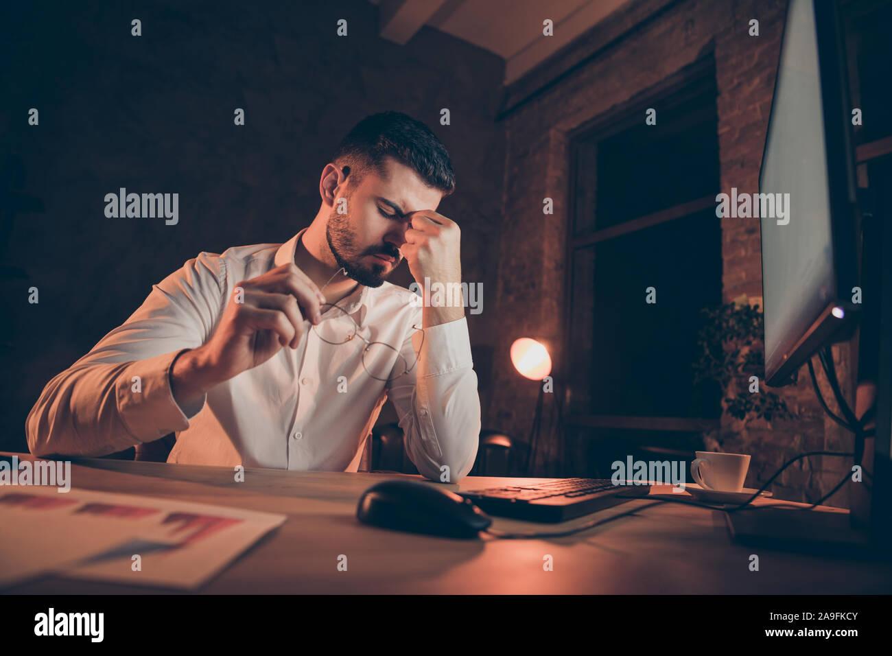 Basso angolo di seguito visualizzare foto di stanchi imprenditore con testa emicrania male gli occhi dolorante di mettere gli occhiali off seduto alla scrivania Foto Stock