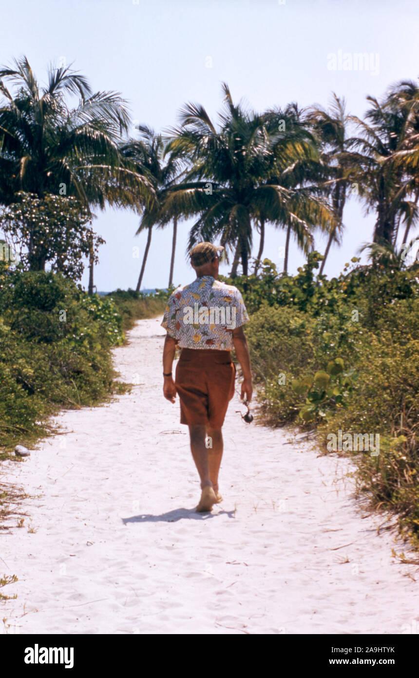 BAHAMAS - aprile 28: vista generale di un vecchio uomo che cammina giù per un sentiero all'oceano mentre trasporta una canna da pesca il 28 aprile 1956 in Bahamas. (Foto di Hy Peskin) (numero impostato: X3731) Foto Stock