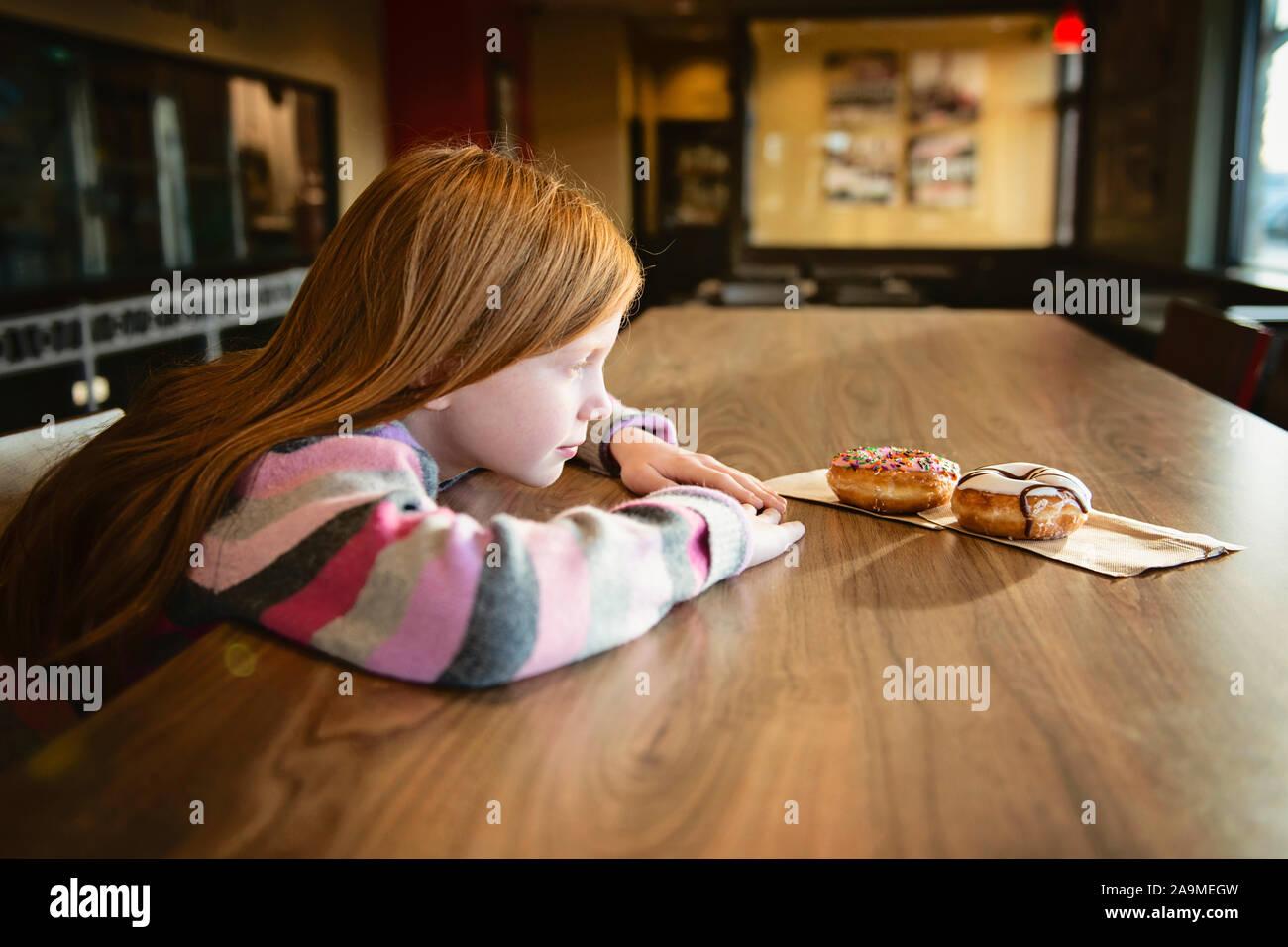 Rosso giovane ragazza dai capelli cercando longingly a deliziose ciambelle Foto Stock