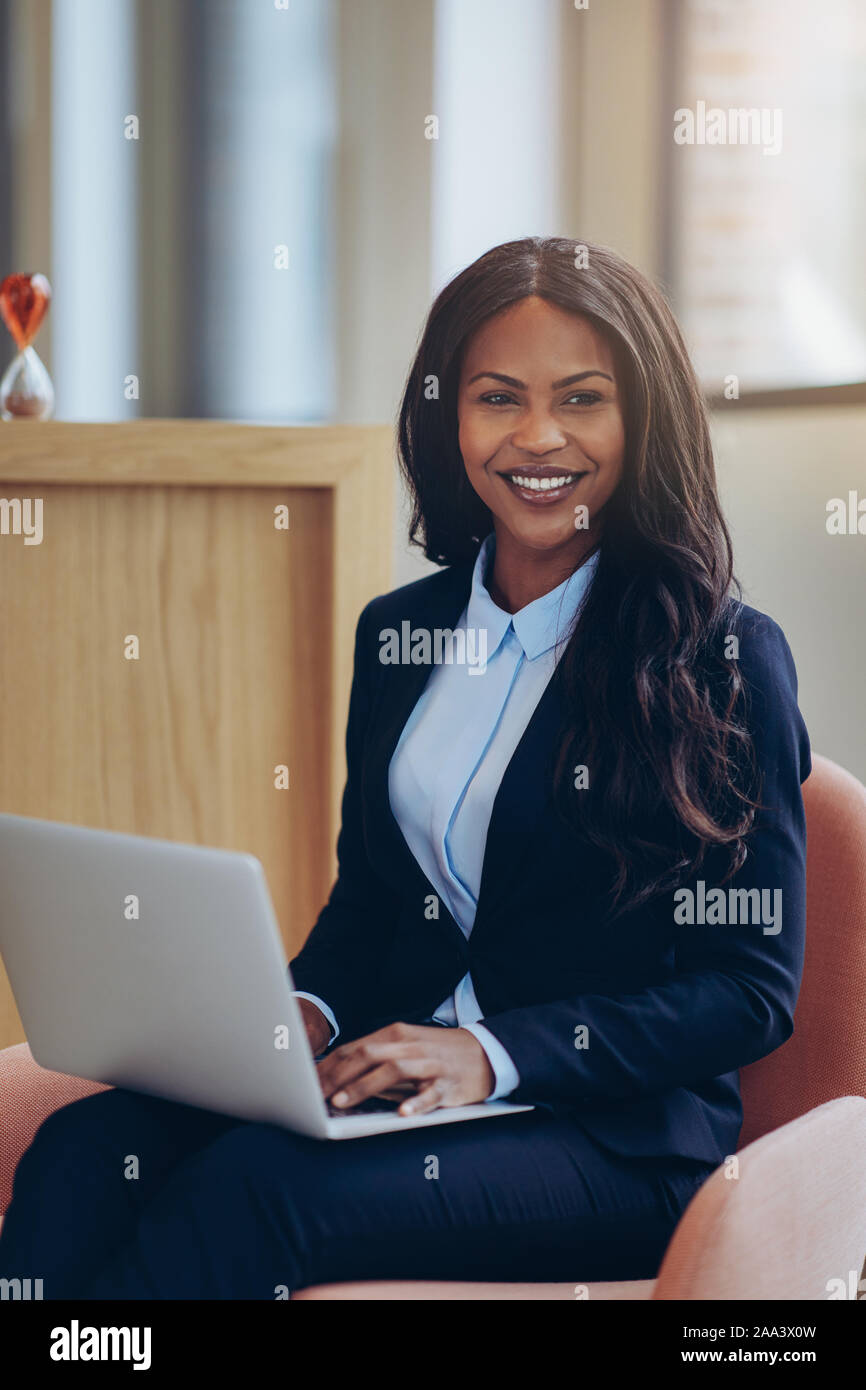 Sorridente giovane americano africano imprenditrice seduto in una sedia nel salotto di un moderno ufficio a lavorare sul suo computer portatile Foto Stock