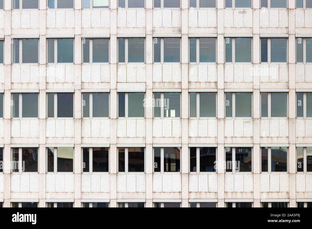 La facciata di colore grigio di un multipiano edificio per uffici con uno schema simmetrico di windows. Foto Stock