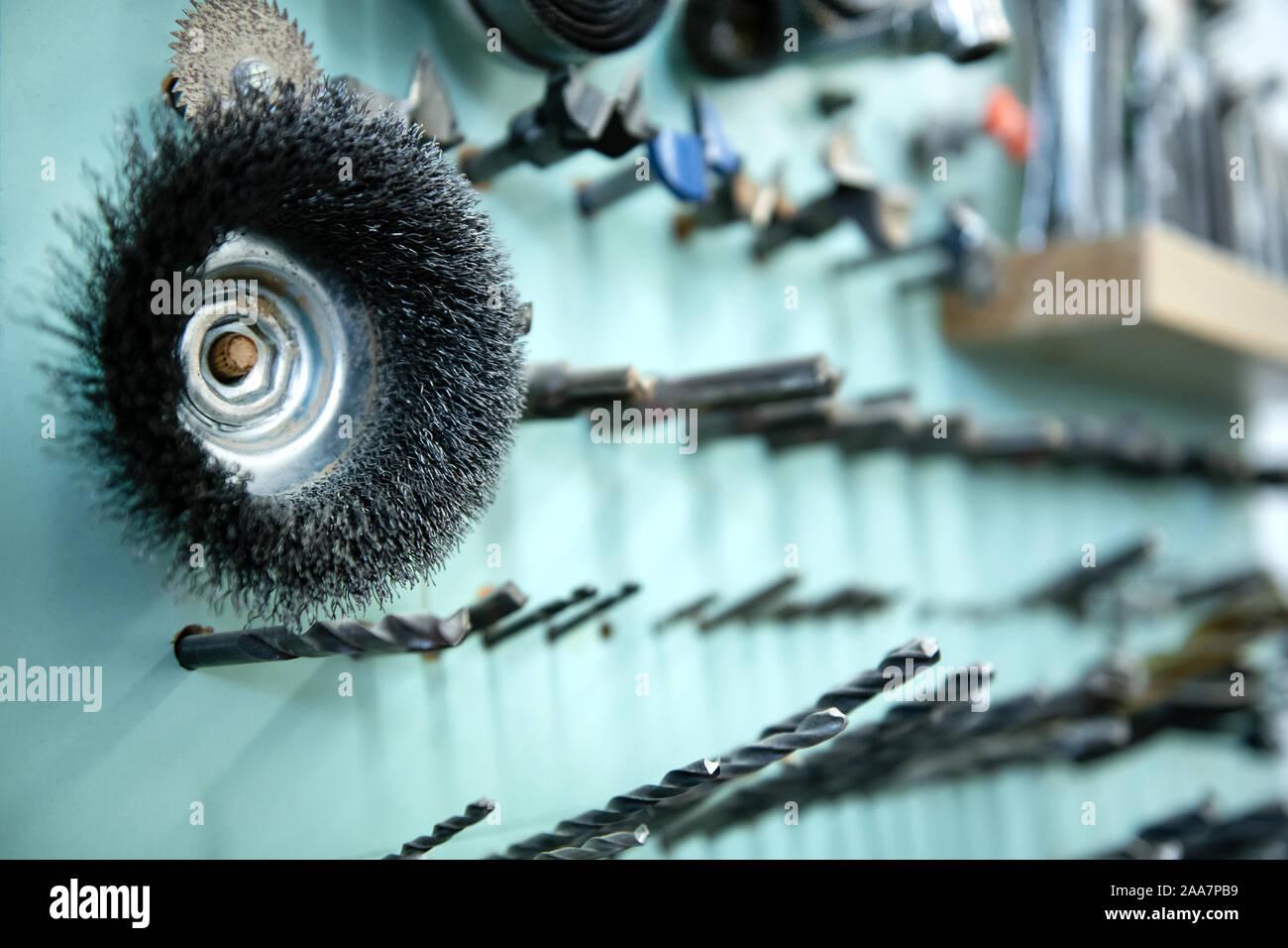 Perfettamente organizzata selezione di utensili per la lavorazione del legno su una parete in un laboratorio di falegnameria in una vista ravvicinata sulle punte da trapano Foto Stock