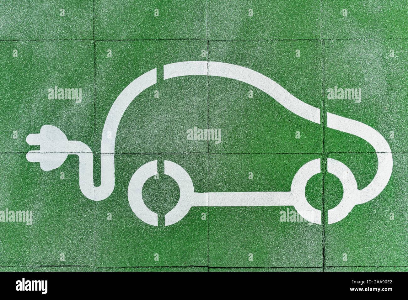 Il simbolo di una vettura con una spina elettrica mostra uno spazio di parcheggio per le auto elettriche Foto Stock