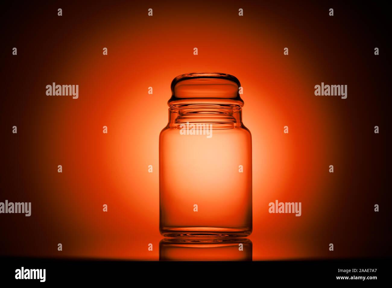 Svuotare il vasetto di vetro su un rosso e sfondo nero Foto Stock