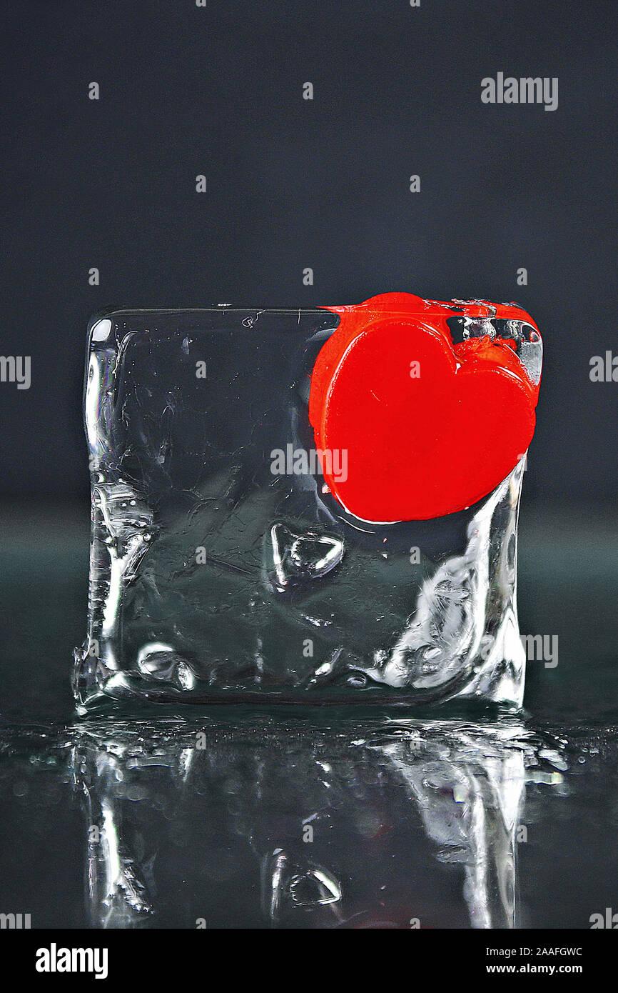 Un piccolo cuore rosso congelato in un cubetto di ghiaccio. Ghiaccio fondente, acqua Foto Stock