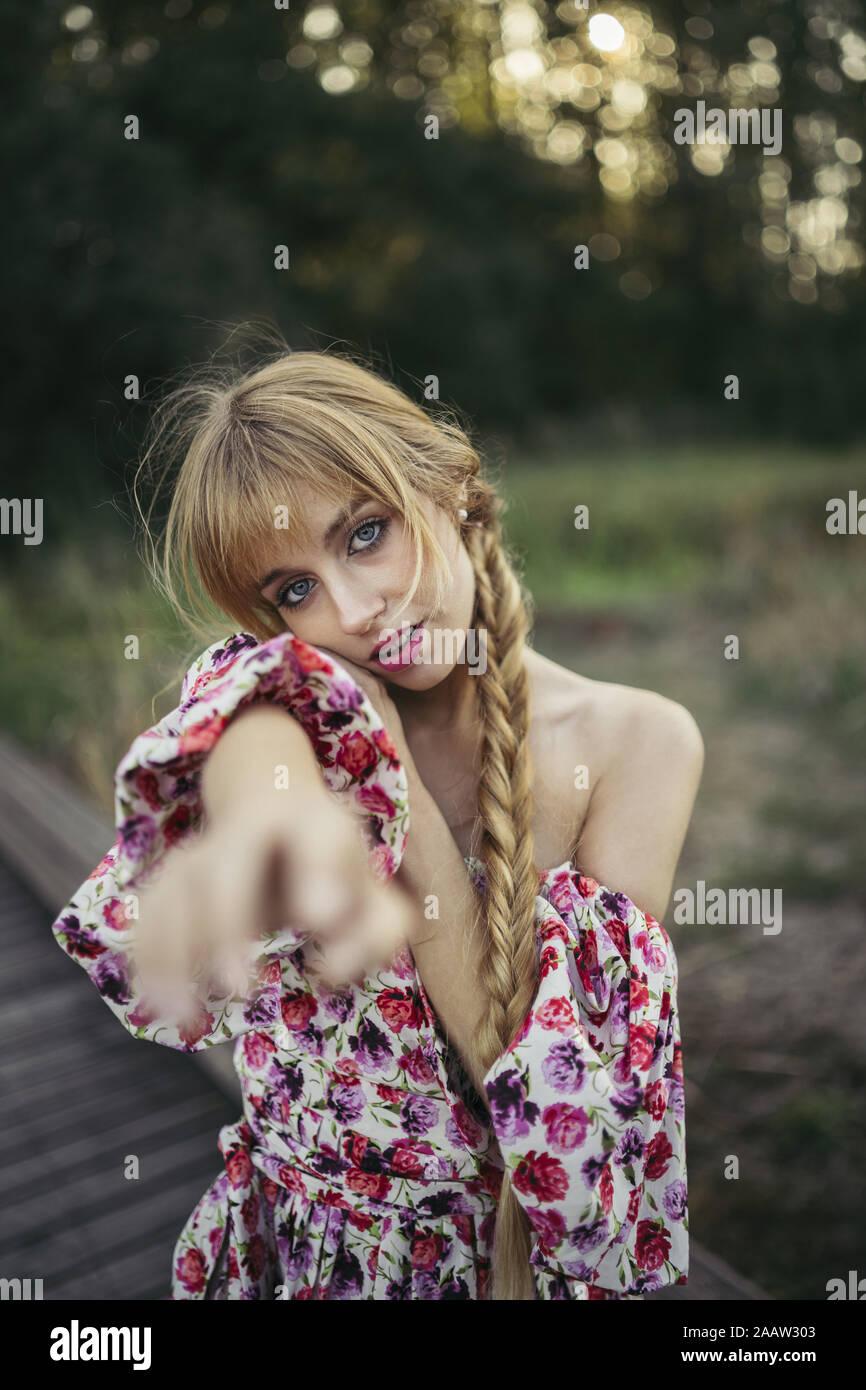 Ritratto di giovane donna con treccia di indossare abiti estivi con disegno floreale alzando la mano Foto Stock