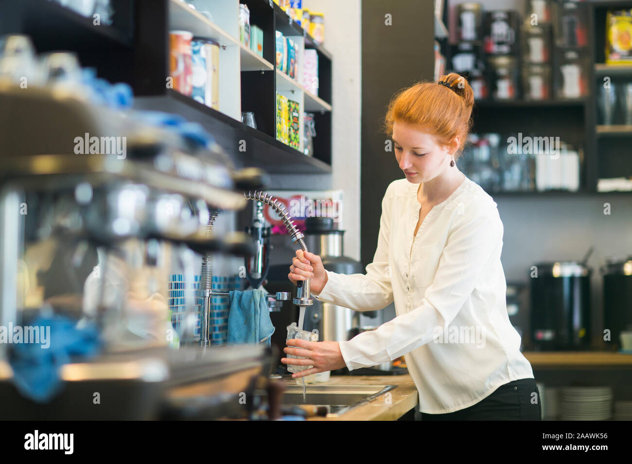 Giovane donna che lavorano nella caffetteria, lavaggio piatti Foto Stock