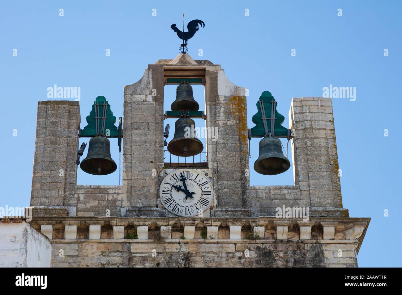 Basso angolo vista della torre campanaria contro il cielo chiaro a Faro, Portogallo Foto Stock