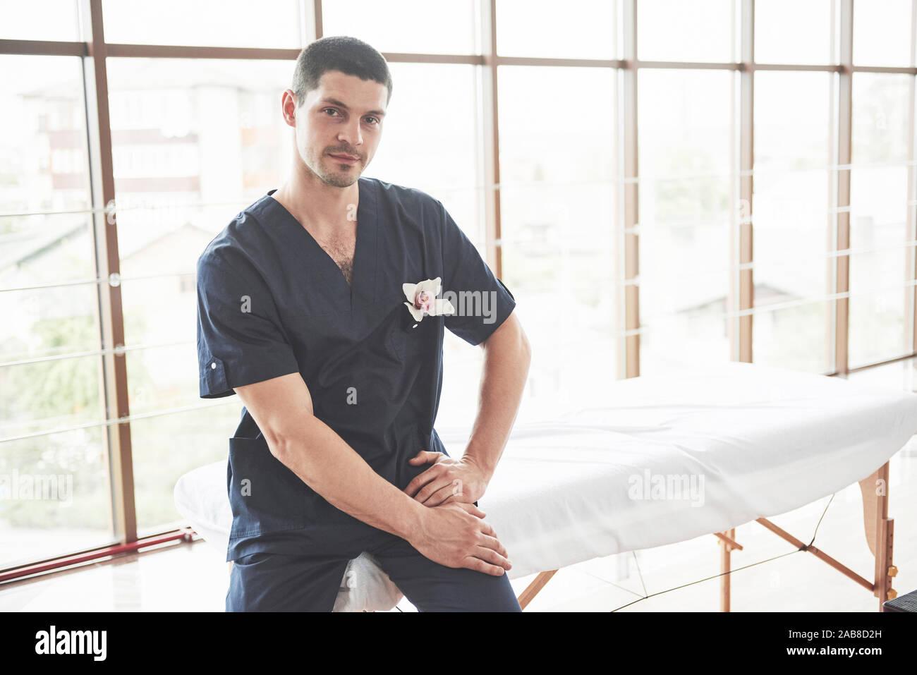 Ritratto di giovane uomo sorridente in uniforme nei pressi di poltrone di massaggio Foto Stock