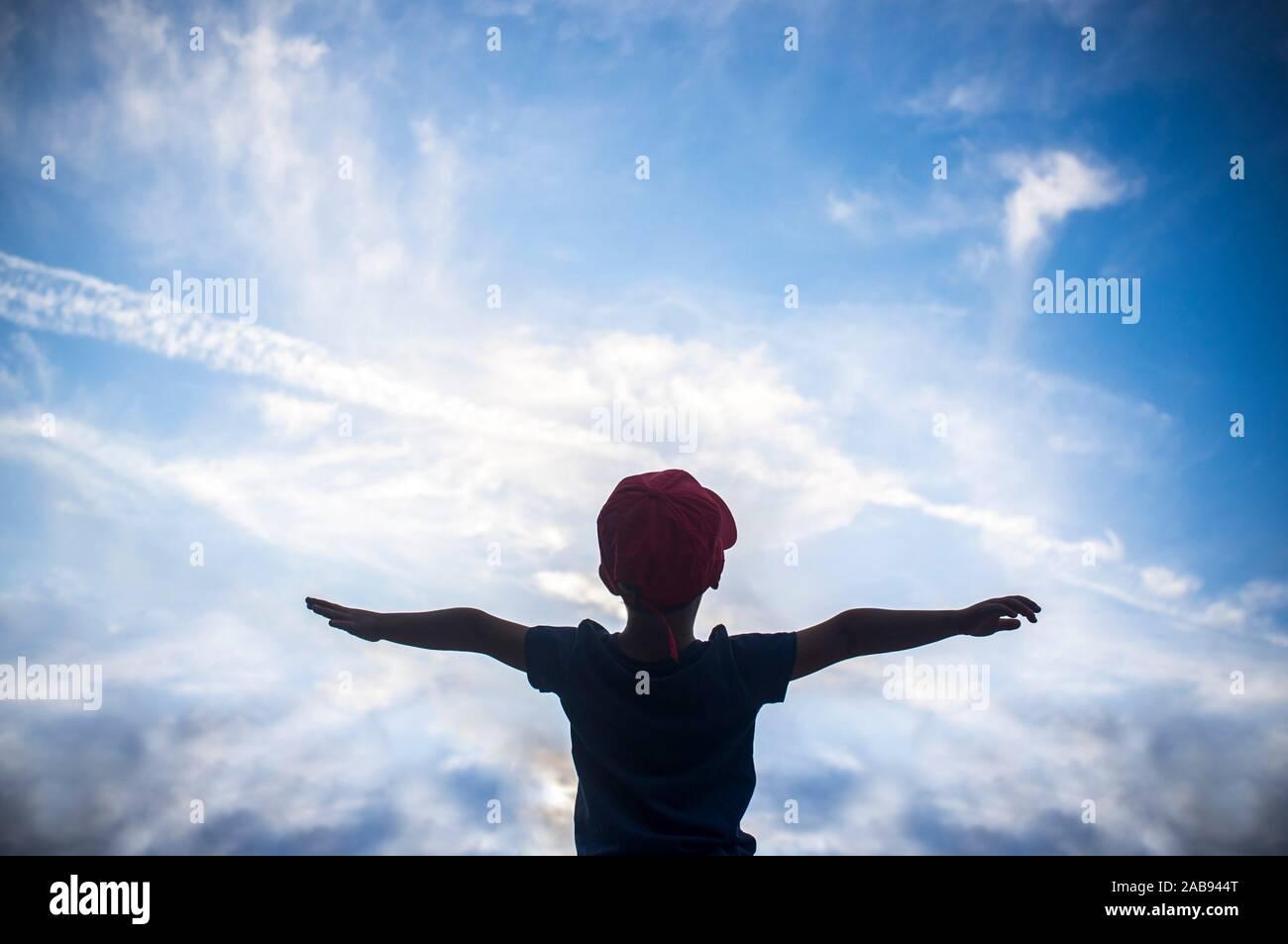 4 anni vecchio ragazzo fingendo di volare al di sopra di cielo nuvoloso. Incoraggiare i bambini fantasia concetto. Foto Stock