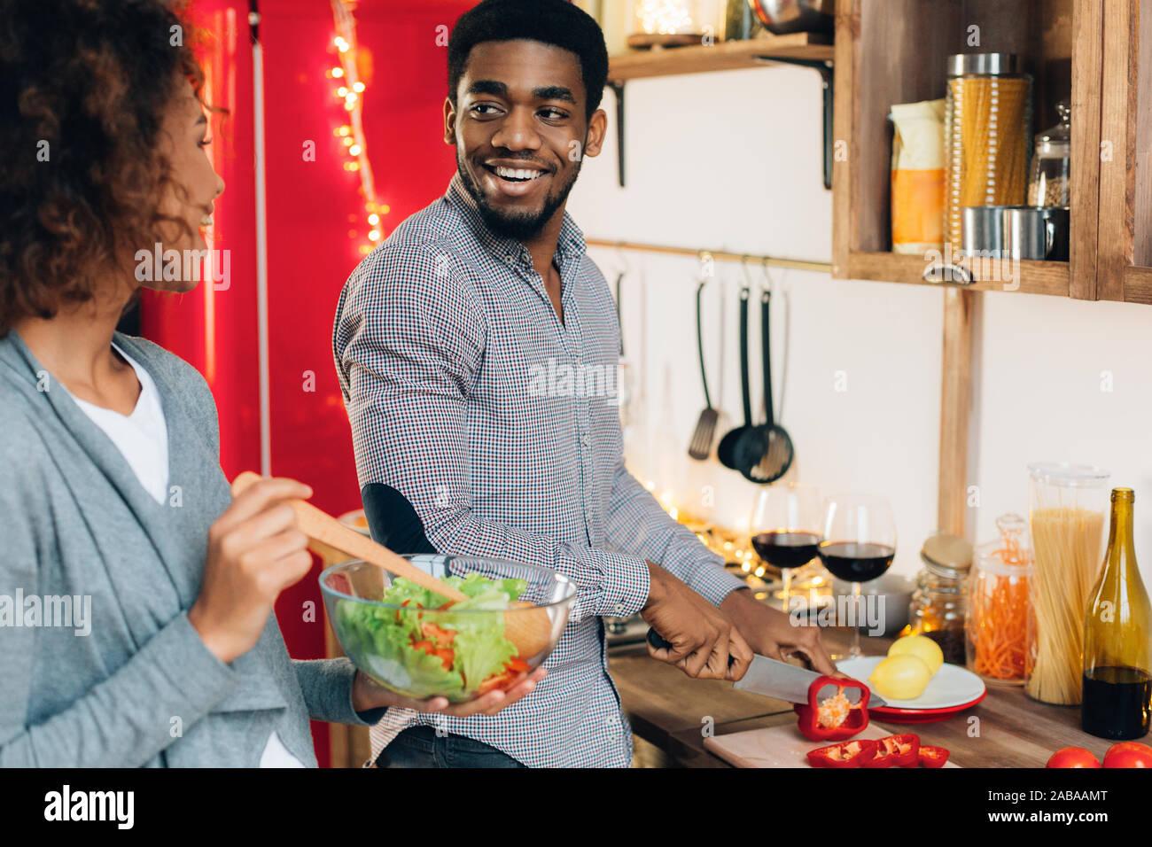 Vegetariano afro-coppia americana insalata di cottura in cucina Foto Stock