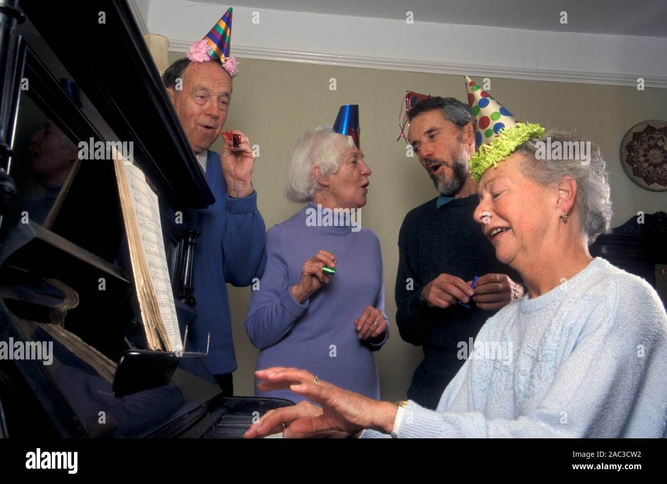 Coppie Senior in party cappelli avente cantare canzone intorno al pianoforte a Natale Foto Stock