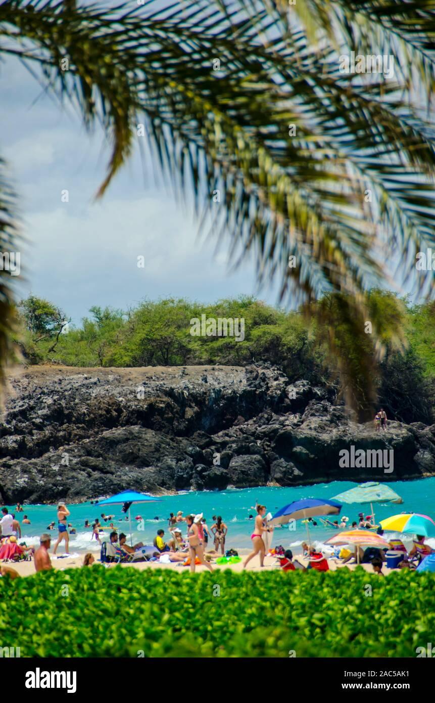 La folla con ombrelloni soddisfare mezzogiorno al Hapuna Beach, lungo Kohala Coast della Big Island. Questa spiaggia di sabbia bianca è stato considerato uno di BES Foto Stock