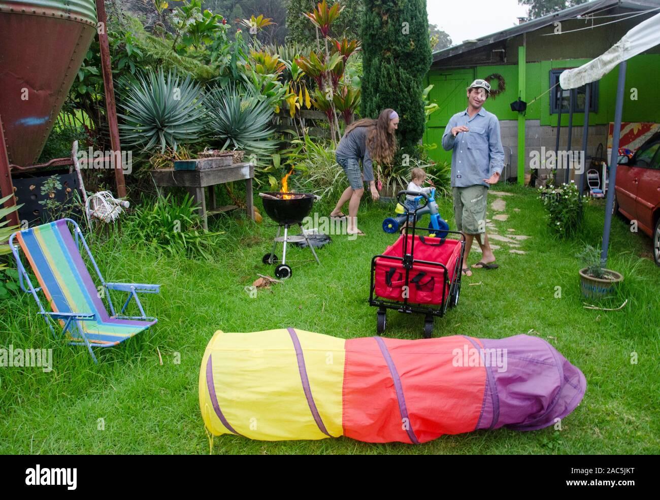 Un giovane locale madre, padre e figlio toddler giocare nel loro cortile con un barbecue a partire e giocattoli sparsi, Big Island. Foto Stock