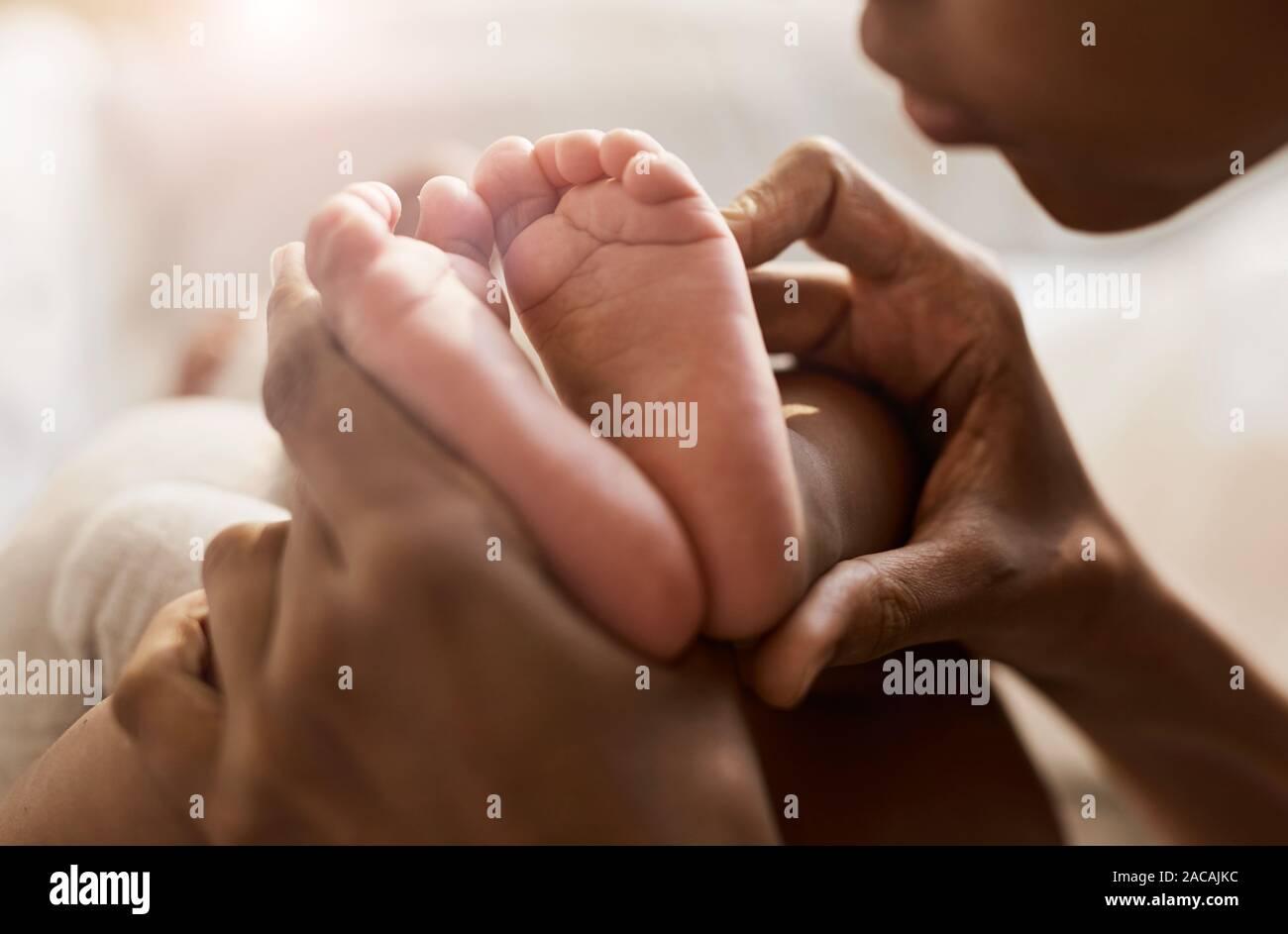 Close up ritratto di donna afro-americana tenendo piccoli piedini di simpatici baby in presenza di luce solare, spazio di copia Foto Stock