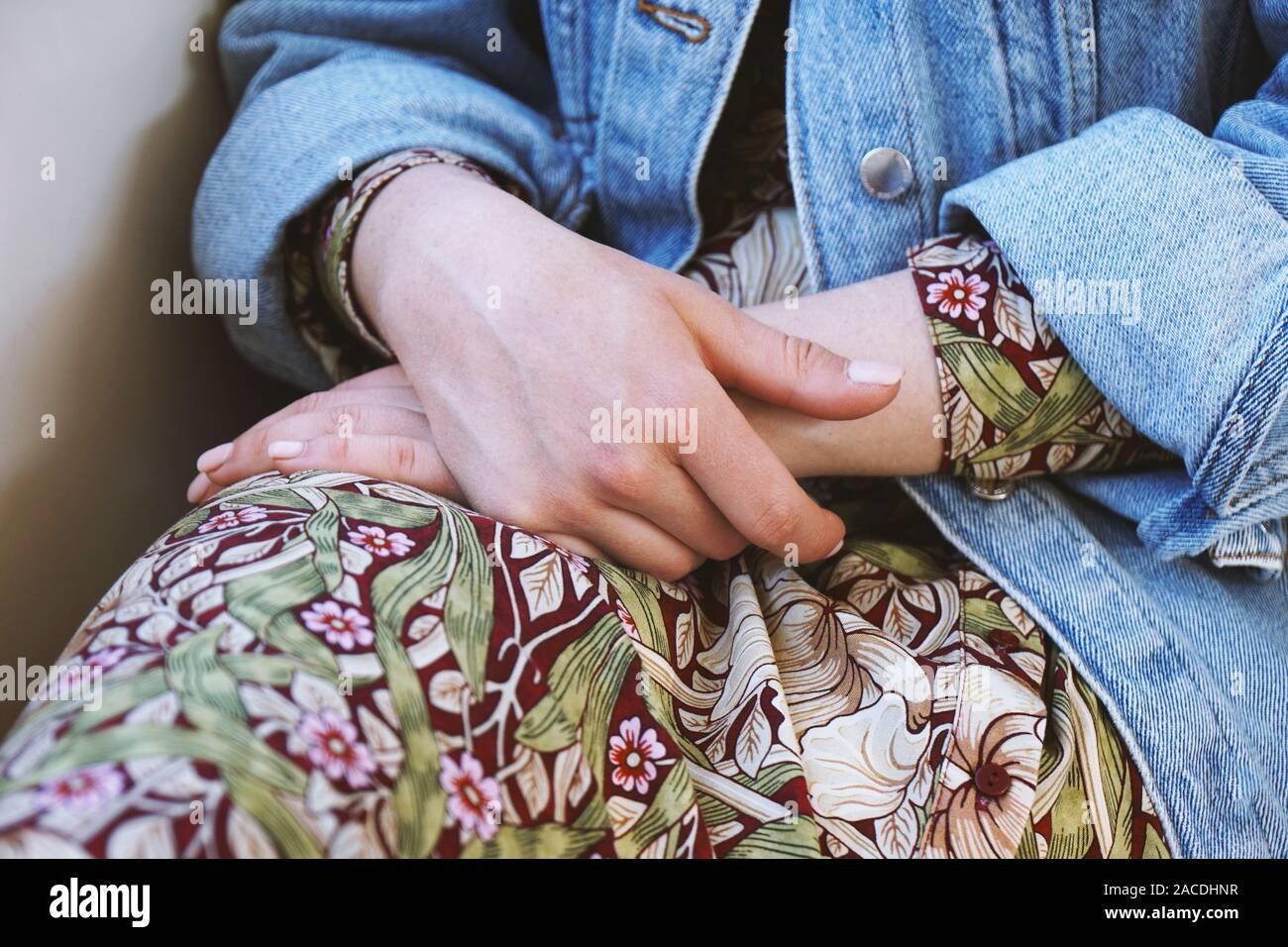 La sezione centrale della giovane donna che indossa il denim camicia al di sopra gli abiti estivi con motivo floreale - close-up di mani femminili ripiegato nel suo giro Foto Stock