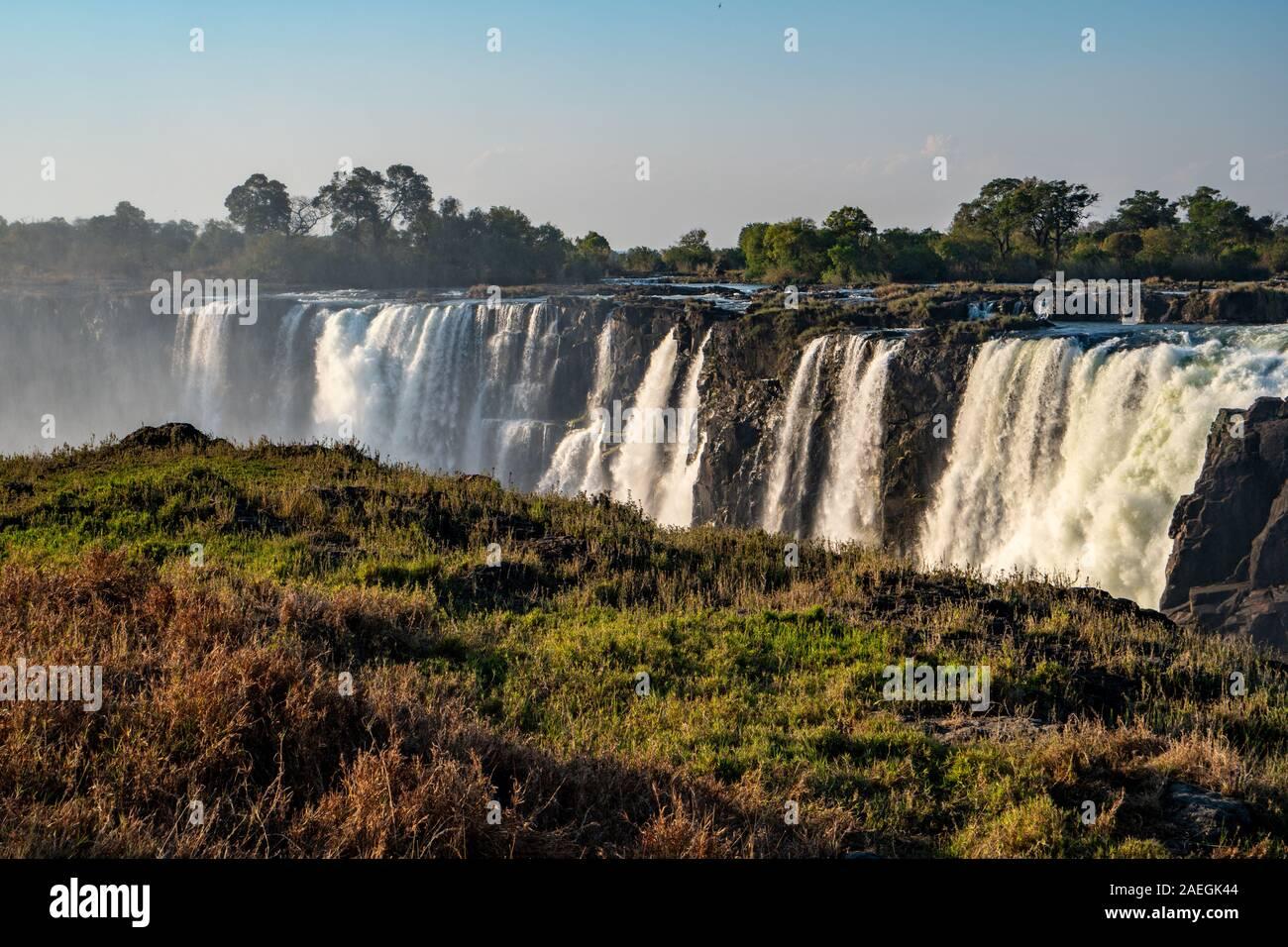 Victoria Falls, che prende il nome da David Livingstone nel 1855 dopo la regina Victoria, la cascata è formata dal fiume Zambesi che cade in un 100 metro profondo ch Foto Stock