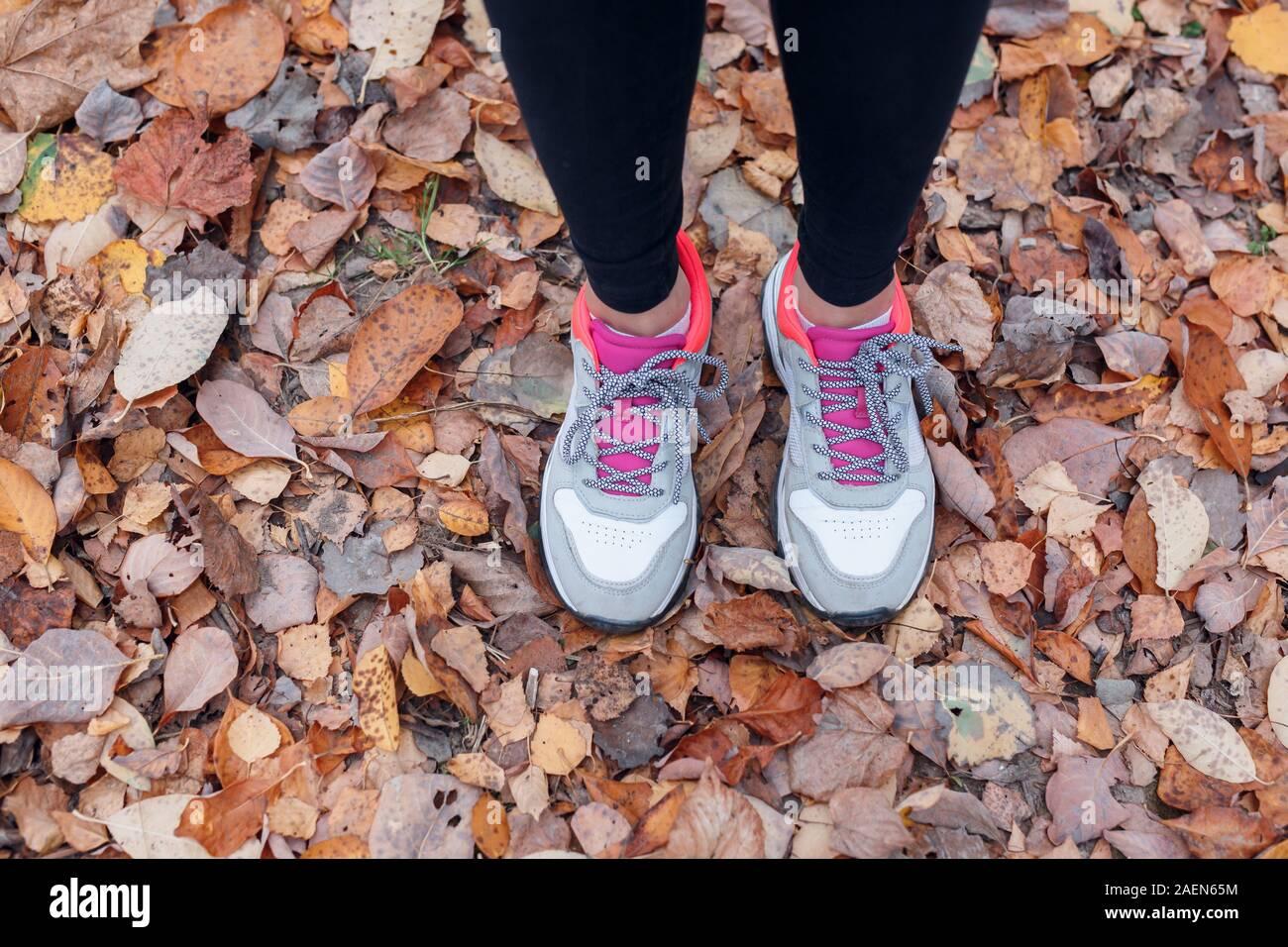 Close-up di piedi di un runner in esecuzione in foglie di autunno nel parco Foto Stock