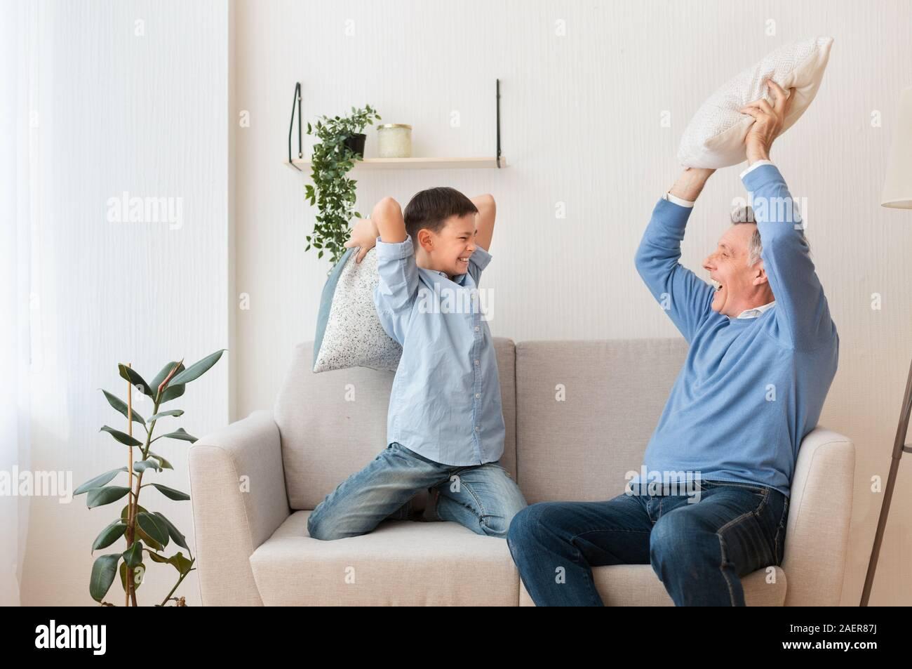 Ragazzo e nonno in lotta con i cuscini sul lettino a casa Foto Stock