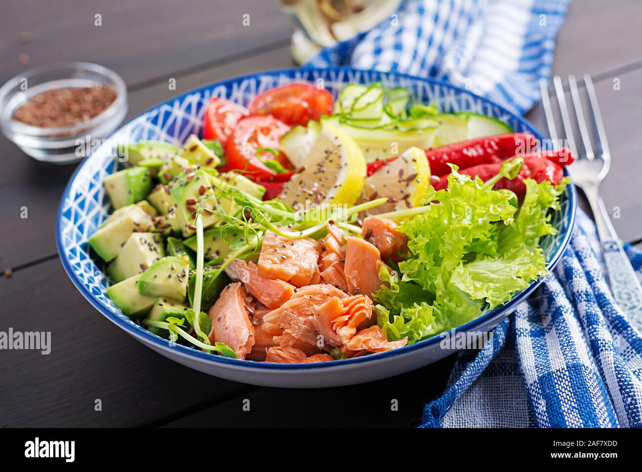 Una sana il salmone grigliato, avocado, pomodoro, cetriolo, paprika e semi di Chia. Pranzo equilibrato in blu ciotola. Ciotola di Buddha. Foto Stock