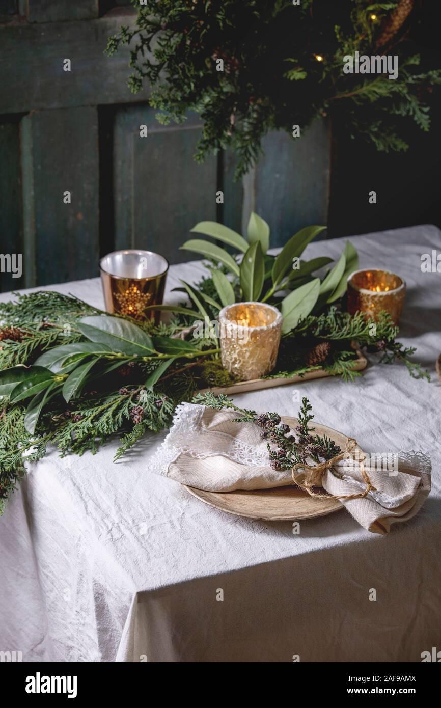 Natale o Capodanno impostazione tabella vuota con piastre in ceramica di tovaglioli, Natale thuja corona, ghirlanda luminosa e candele accese sul tableclo bianco Foto Stock