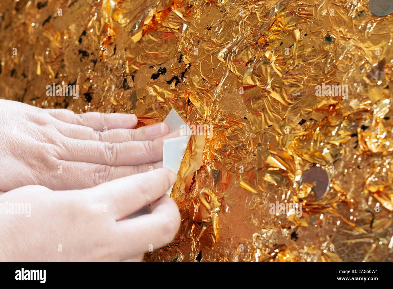 Mano di doratura buddista oro foglietto sulla palla dorata nel tempio per pregare e adorare il buddha Foto Stock
