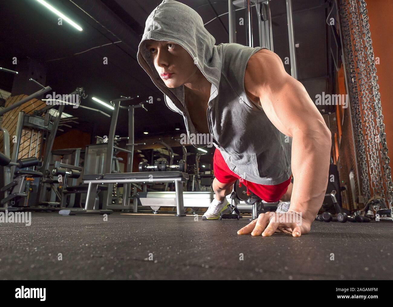 Giovane uomo sportivo facendo spingere ups esercitare con una mano in una palestra per il fitness. Uno stile di vita sano concetto Foto Stock