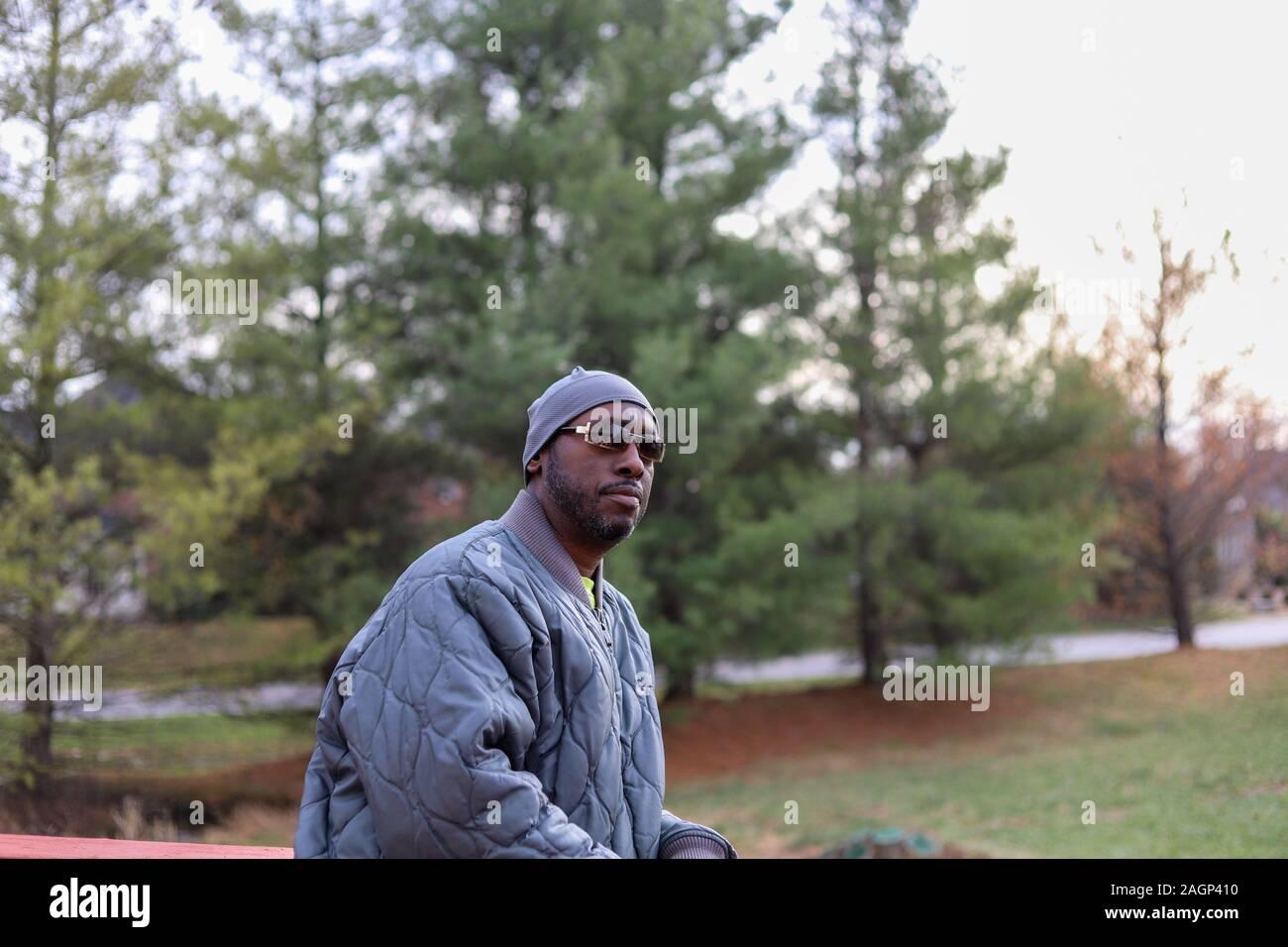 Un ritratto di un afro-americano di uomo in piedi fuori in grigio di una giacca invernale Foto Stock