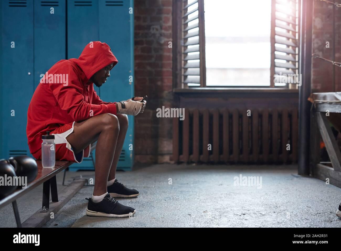 Boxer muscolare in abbigliamento sportivo seduta sul banco di lavoro e utilizzando il suo telefono cellulare in spogliatoio Foto Stock