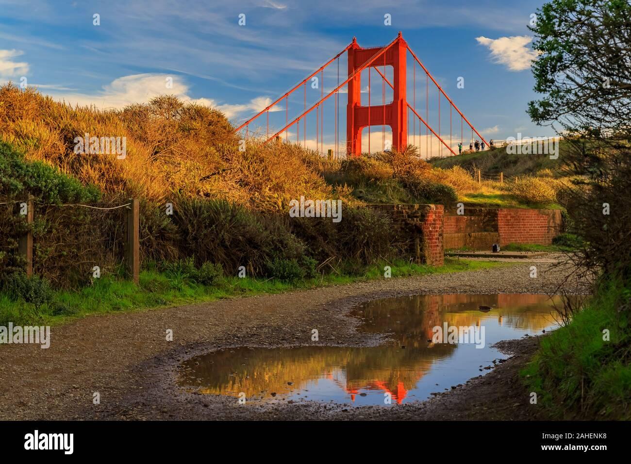 Panorama di San Francisco Golden Gate bridge in Marin Headlands California riflettendo in una pozzanghera dopo la pioggia con soffici nuvole in background Foto Stock