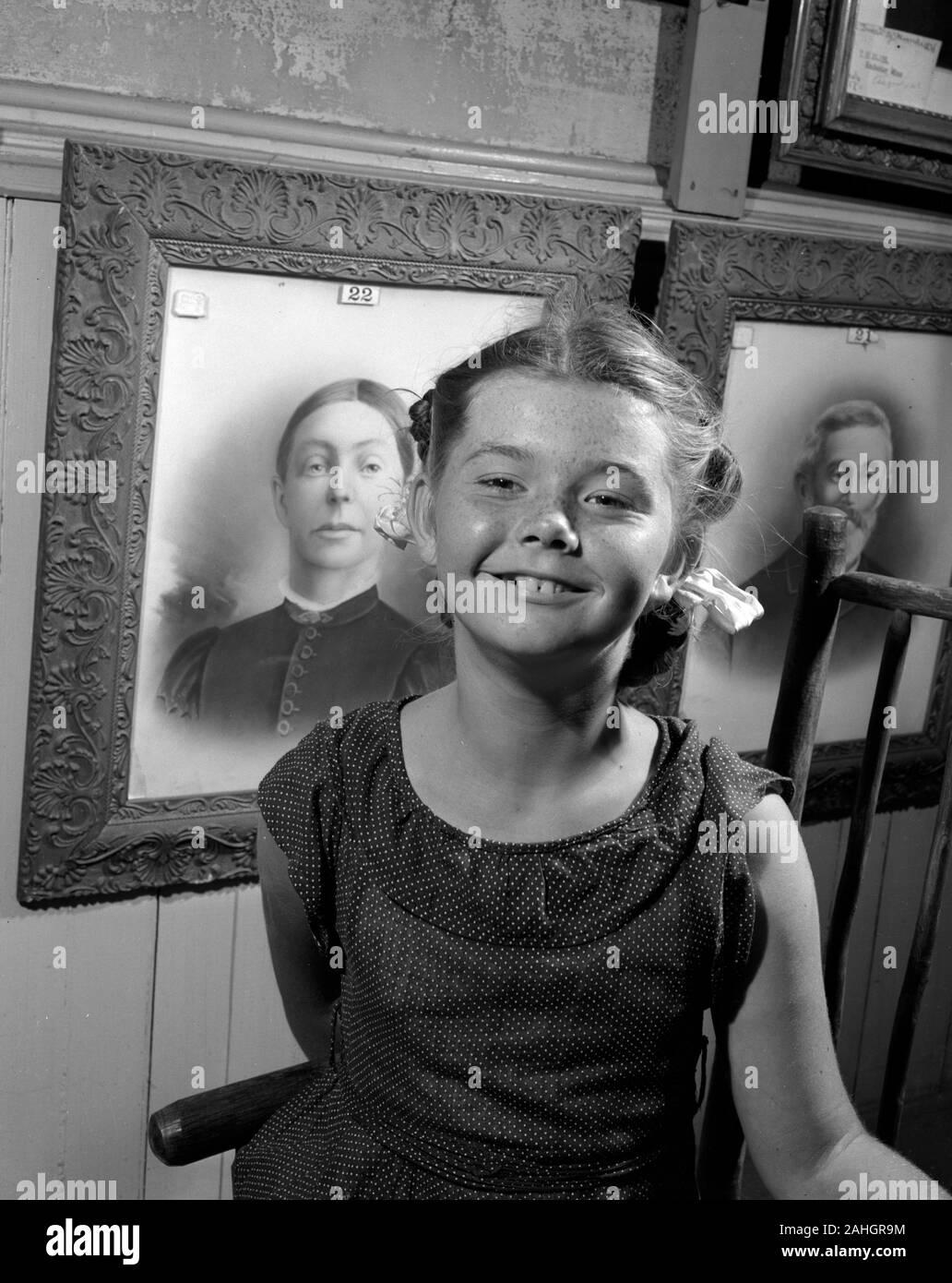 Ragazza in piedi di fronte a ritratti di membri della famiglia 1946. Questo era parte del Minnesota State Fair nel 1946, dove la gente si fermò di fronte dei ritratti dei loro nonni per illustrare caratteristiche genealogiche. Foto Stock