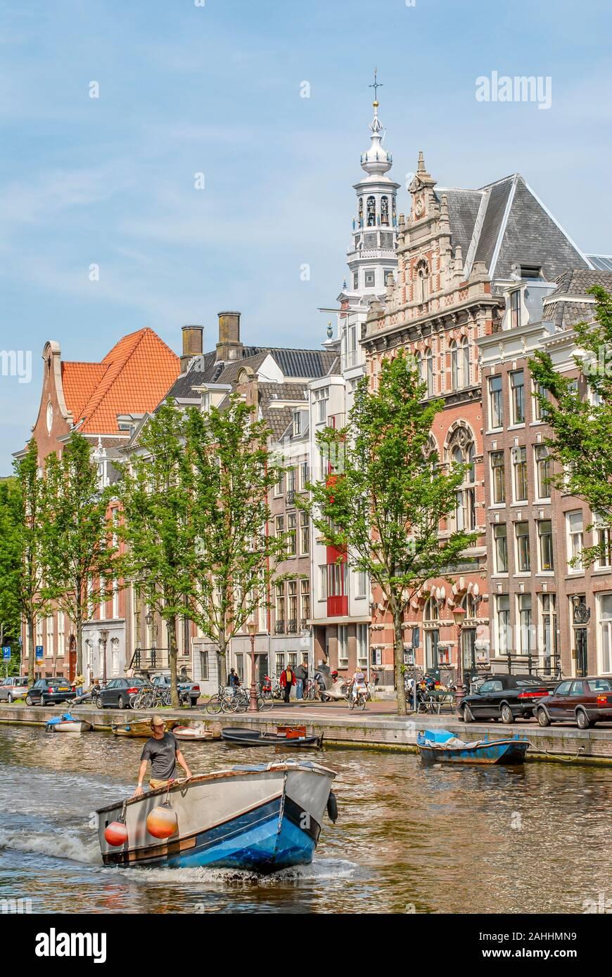 Piccola barca in esecuzione attraverso un Amsterdam Canale d'acqua Netherlande Foto Stock