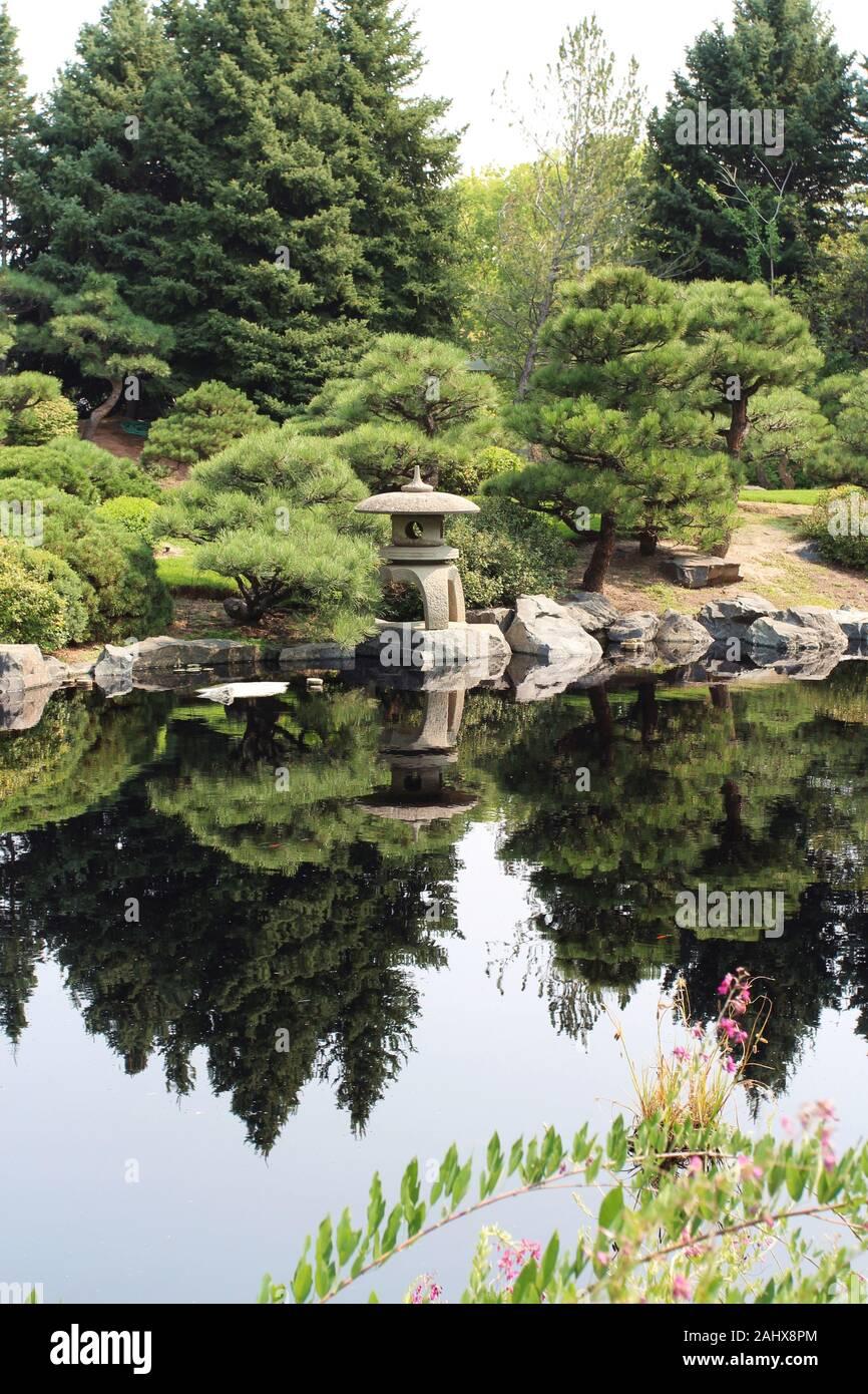 Un giardino in stile Giapponese con una lanterna di pietra e vari coltivati alberi sempreverdi accanto a un lago, con il paesaggio riflessi nell'acqua a colori Foto Stock