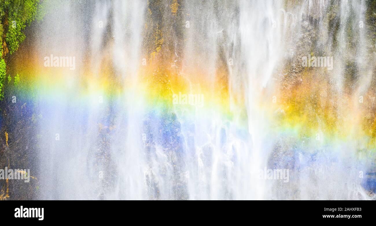 Vista ravvicinata della Tumpak Sewu cascate noto anche come Coban Sewu con un bellissimo arcobaleno formata dalla rifrazione della luce in goccioline d'acqua. Foto Stock