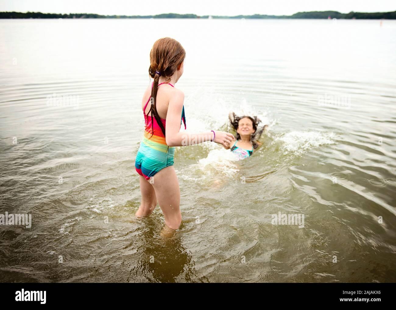 Due giovani ragazze in costume da bagno che giocano in un lago Foto Stock