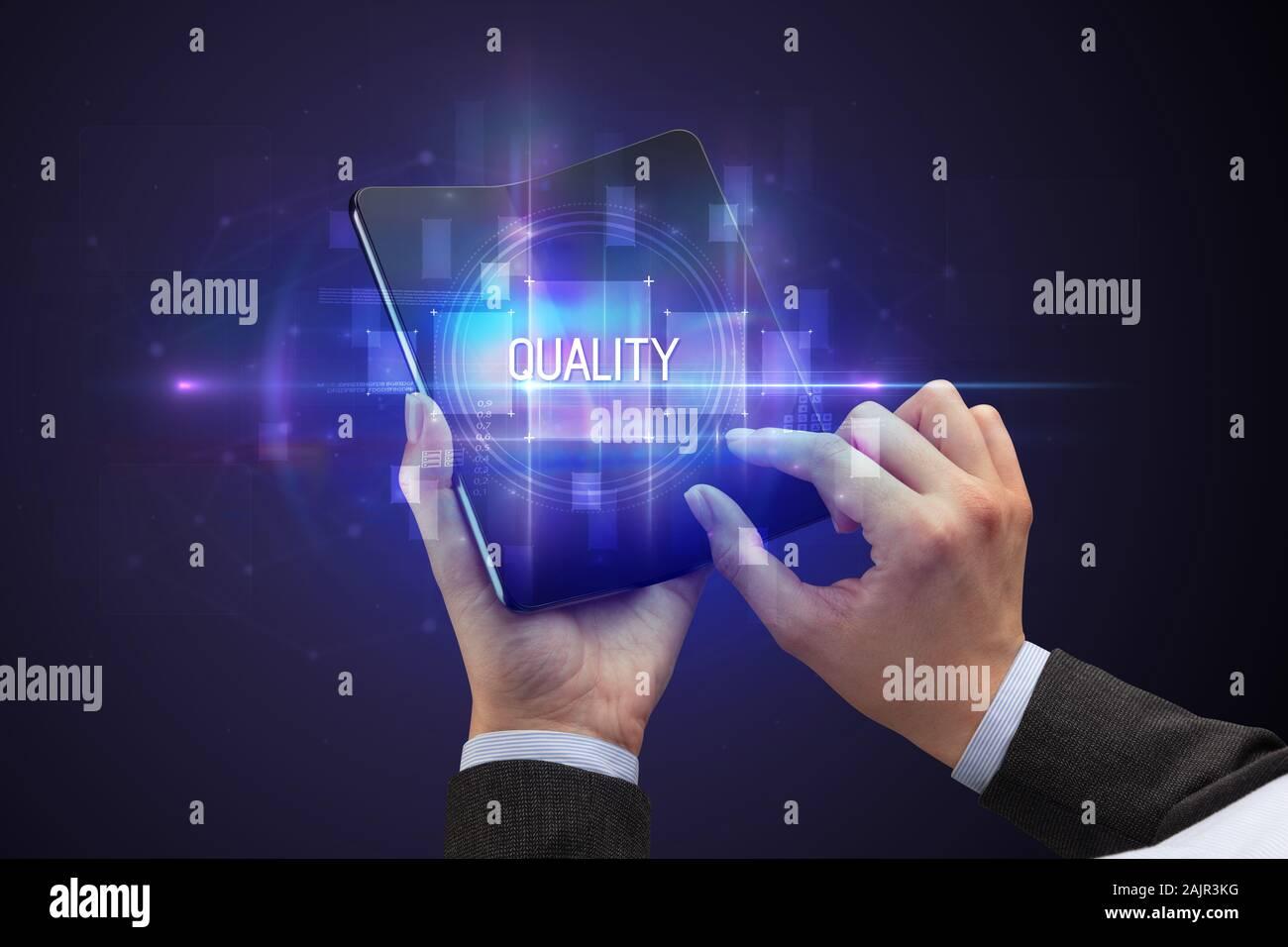 Imprenditore tenendo un smartphone pieghevole con qualità iscrizione, nuovo concetto tecnologico Foto Stock