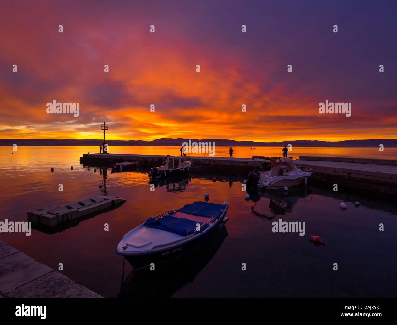I pescatori prima del tramonto paesaggio nel piccolo porto di Malinska Croazia cielo gloriosa pacifica seawall atmosferica Ribarsko selo Haludovo Quarnaro Foto Stock