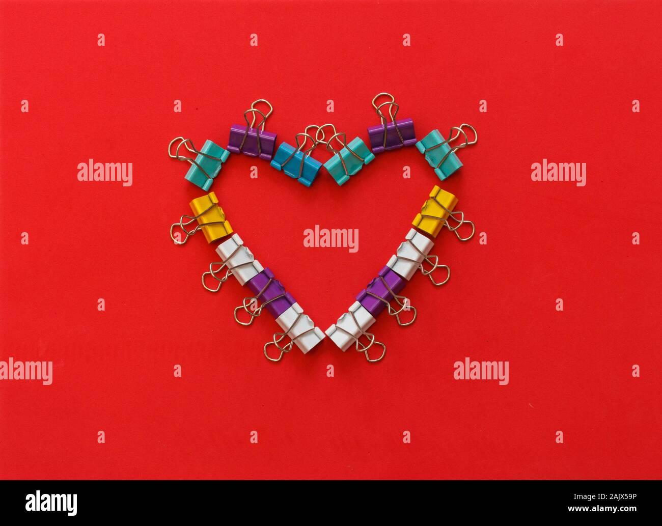 Multicolore ufficio di metallo fermagli per carta formando forma di cuore Foto Stock