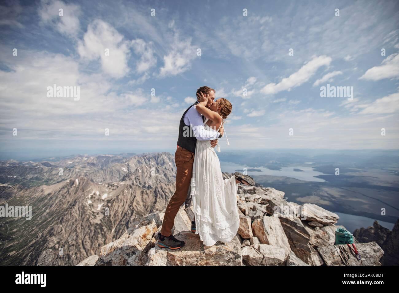 La coppia appena fatta ha il primo bacio durante il matrimonio sulla cima della montagna, Wyoming. Foto Stock
