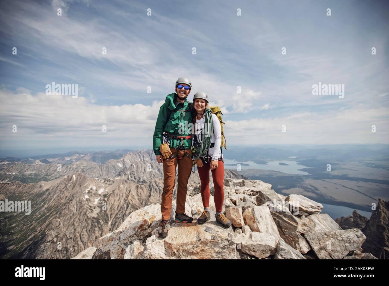 Uomini e donne climber sorridono dopo aver sommite il Grand Teton, Wyoming Foto Stock