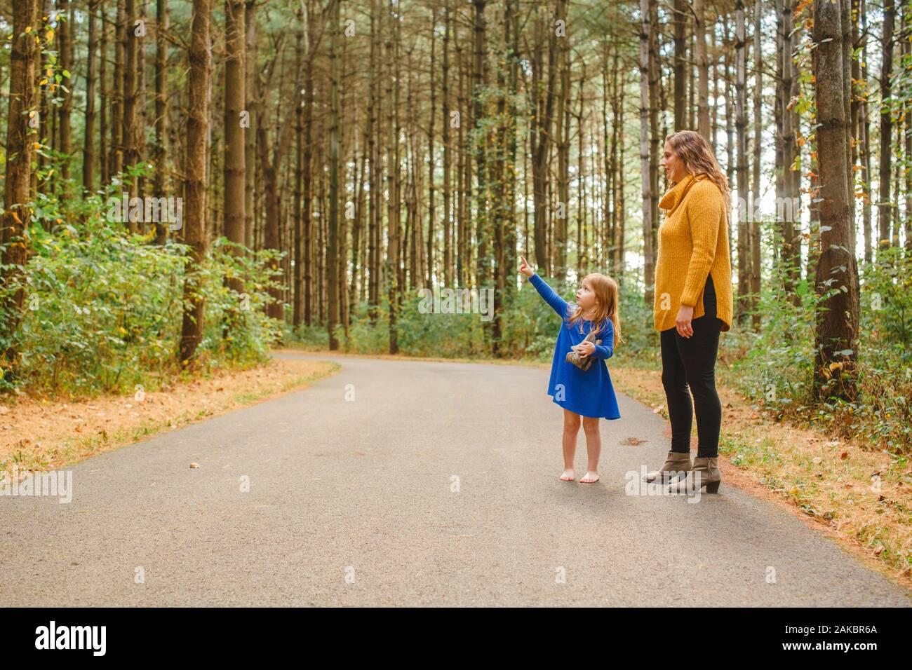 Un bambino piccolo si alza su un sentiero boscoso con la madre che punta in su Foto Stock