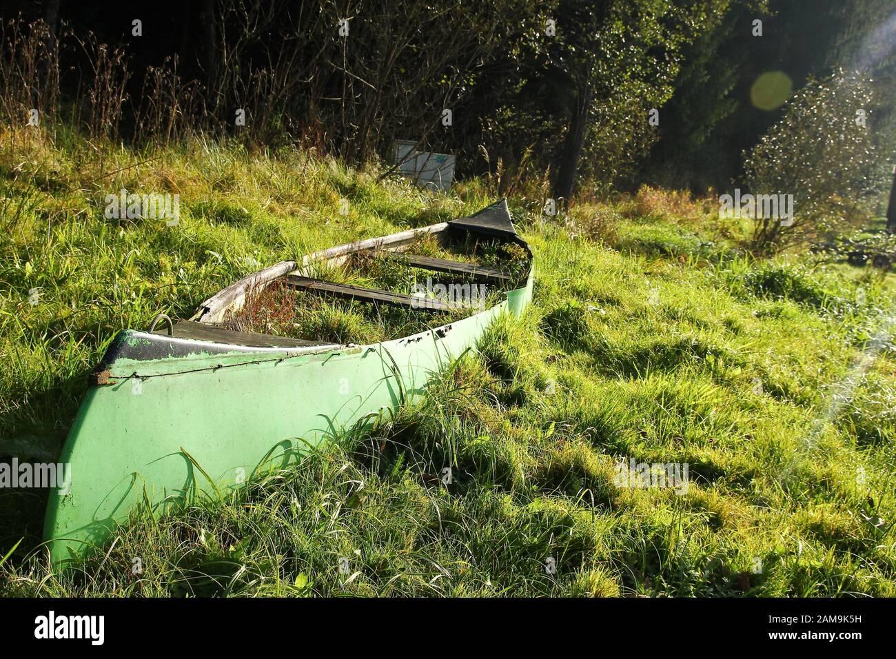 La vecchia canoa è adagiata sul prato vicino al fiume ed è abbandonata, piena di erba e inutile. Foto Stock