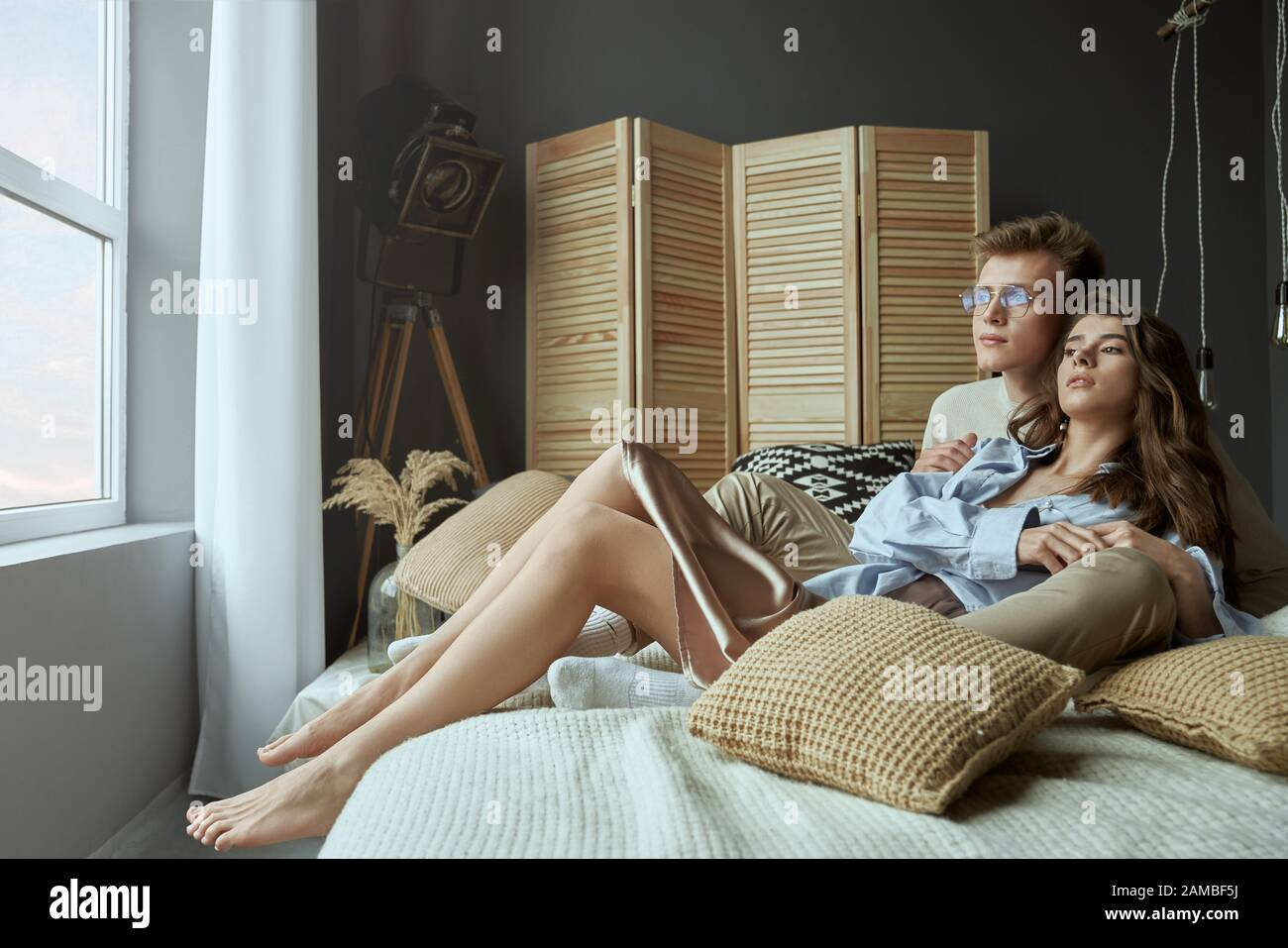 Vista frontale della dolce coppia giovane felice seduto e abbracciato sul letto a casa. Giovane ed elegante ragazza brunetta sdraiata e rilassante in braccia di ragazzo sorridente in occhiali. Concetto di amore, rapporto. Foto Stock