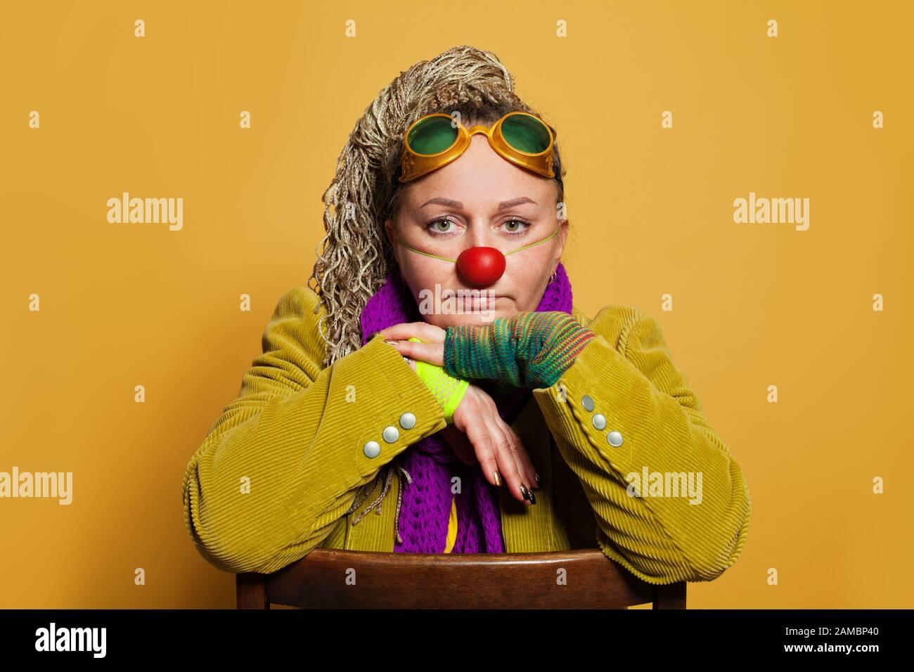 Psicologo donna matura in costume clown per prestazioni in ospizio per bambini su sfondo giallo. Ritratto di persone reali Foto Stock