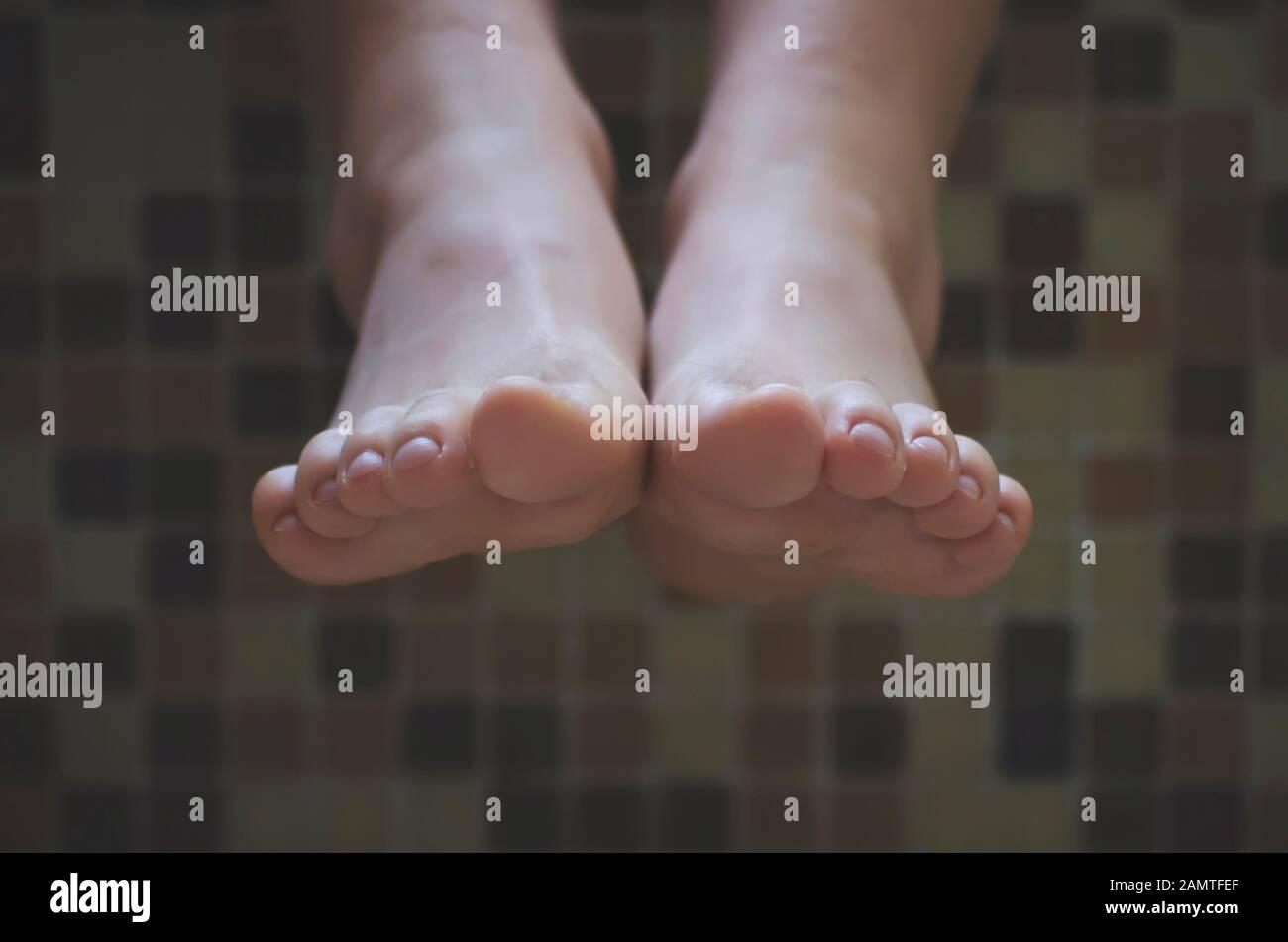 Primo piano dei piedi di una ragazza appesi sul bordo di un bagno Foto Stock