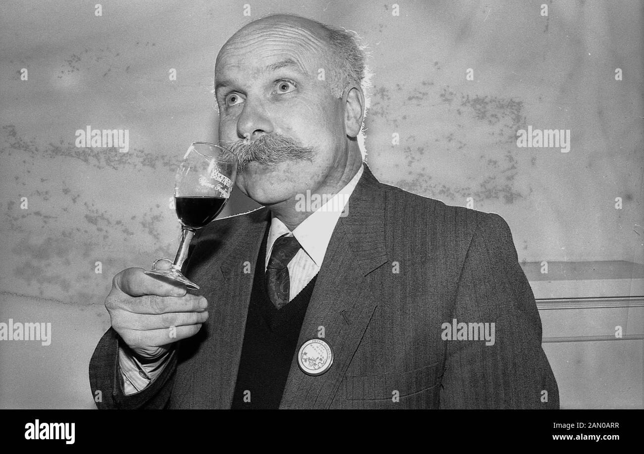 1988, storico, una mezza età gentiluomo di una degustazione di vino, roteare il calice per rilasciare il vino del bouquet e poi annusare il vino, per catturare il sapore con il suo naso. Foto Stock