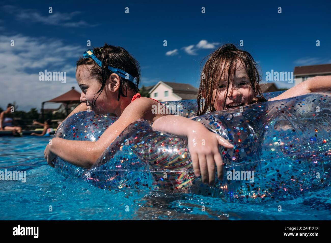 ragazze felici che giocano in piscina galleggiano insieme mentre nuotano Foto Stock